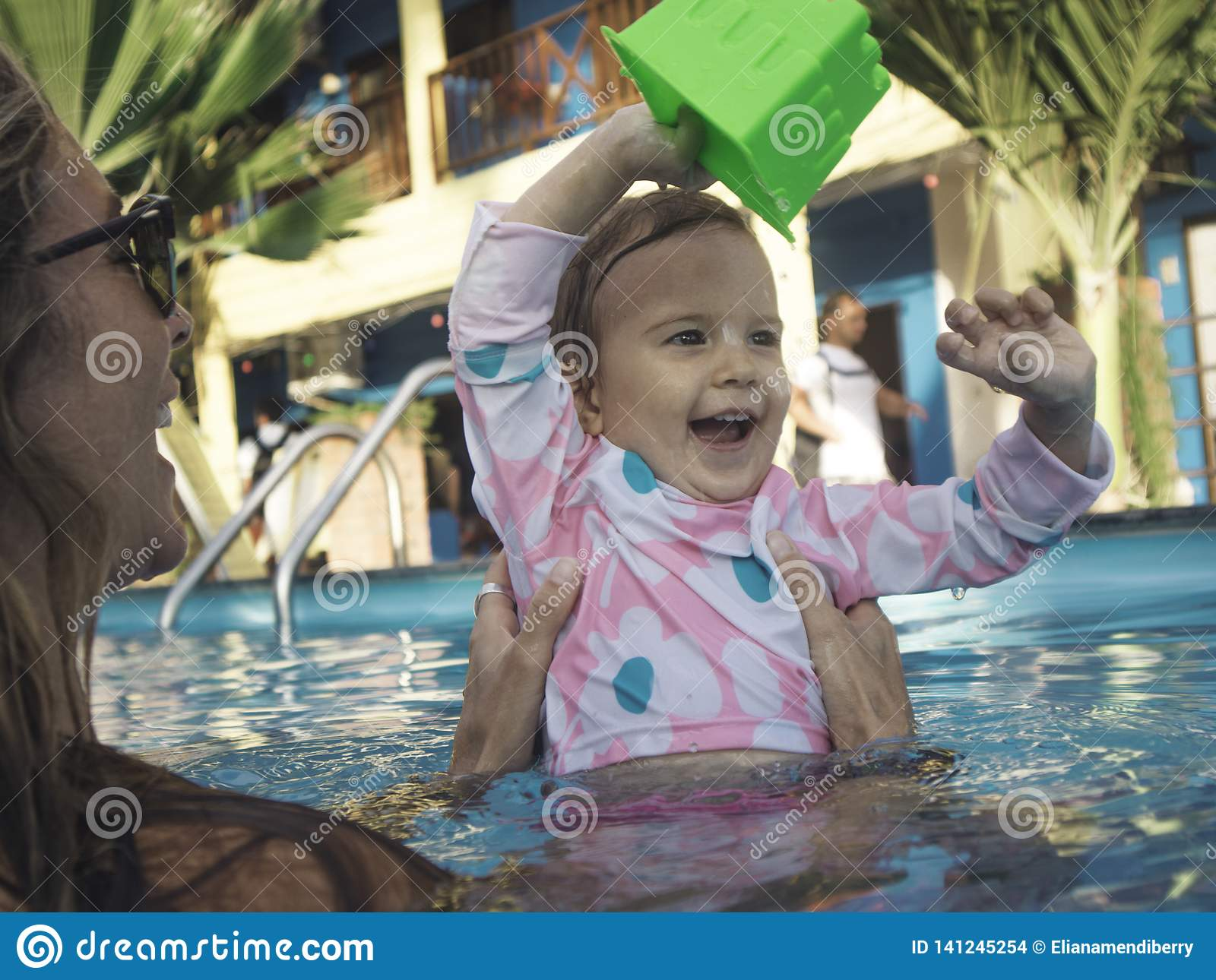 Mother Enjoying A Summer Day On The Swimming Pool with her Family