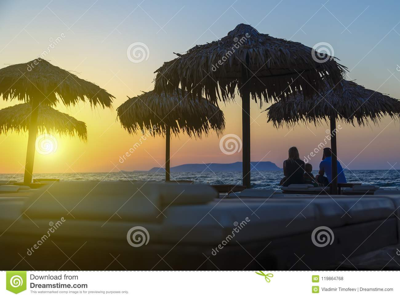 Silhouette of happy people which watching sunset time on the beach. They having fun on the nature. Concept of happy