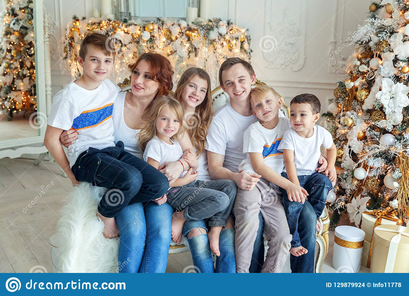 Mother father and five children near Christmas tree at home