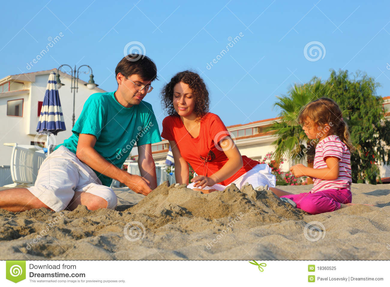 Mother with father and girl sit on beach