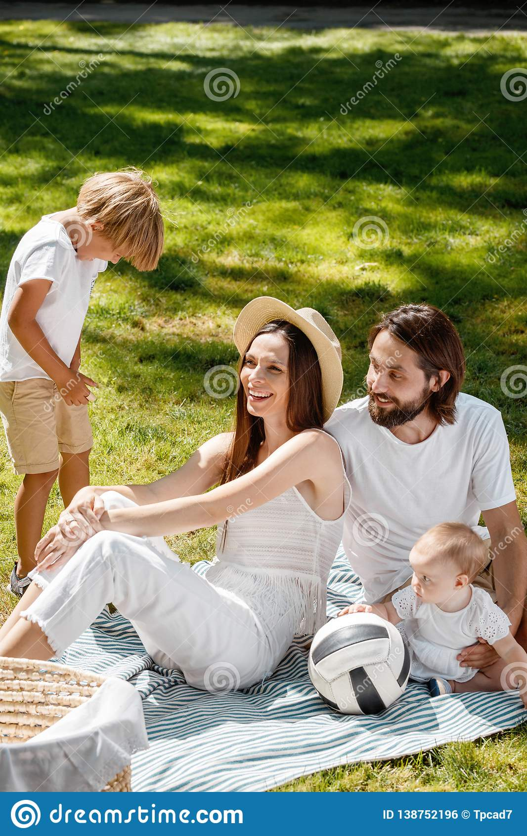 Mother, father, their son and little daughter, dressed in white clothes, take rest on the picnic in the park. Happy