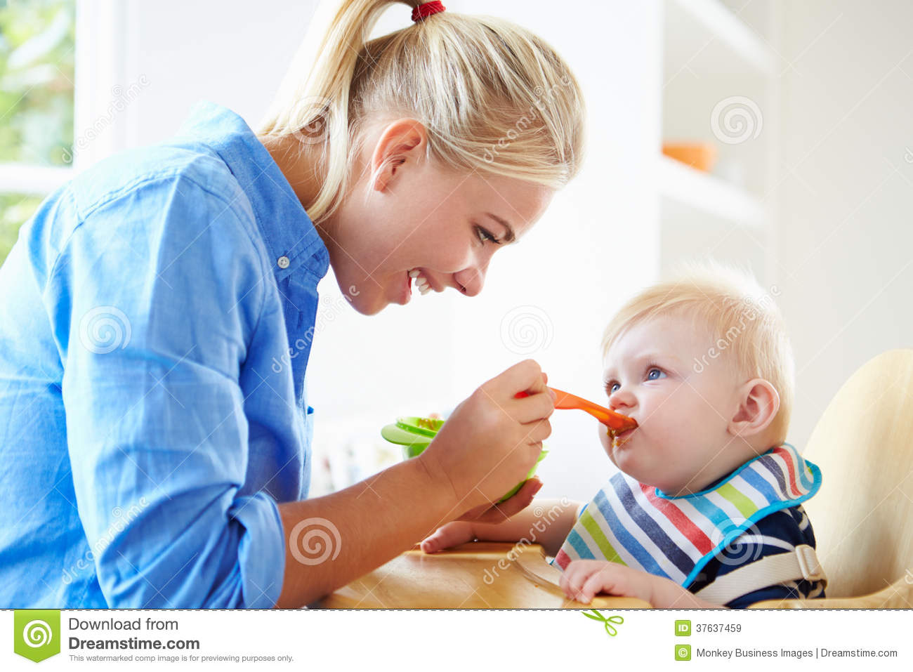 Mother Feeding Baby Boy In High Chair Royalty Free Stock