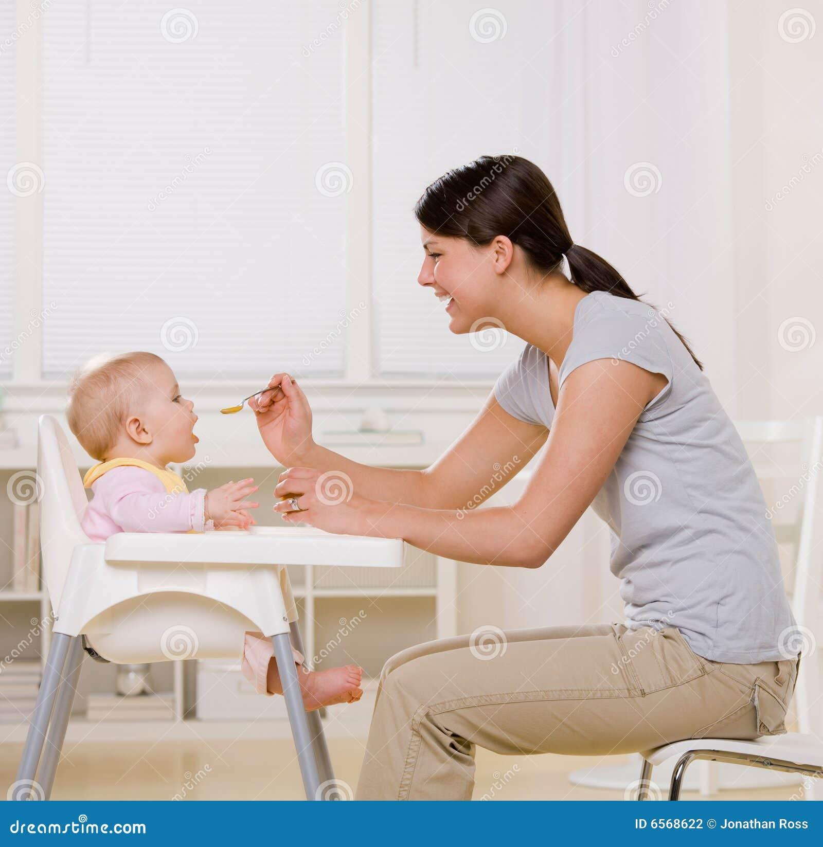 Mother Feeding Baby In Highchair In Kitchen Stock