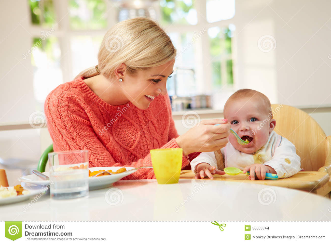 Mother Feeding Baby Sitting In High Chair At Mealtime Stock Images ...