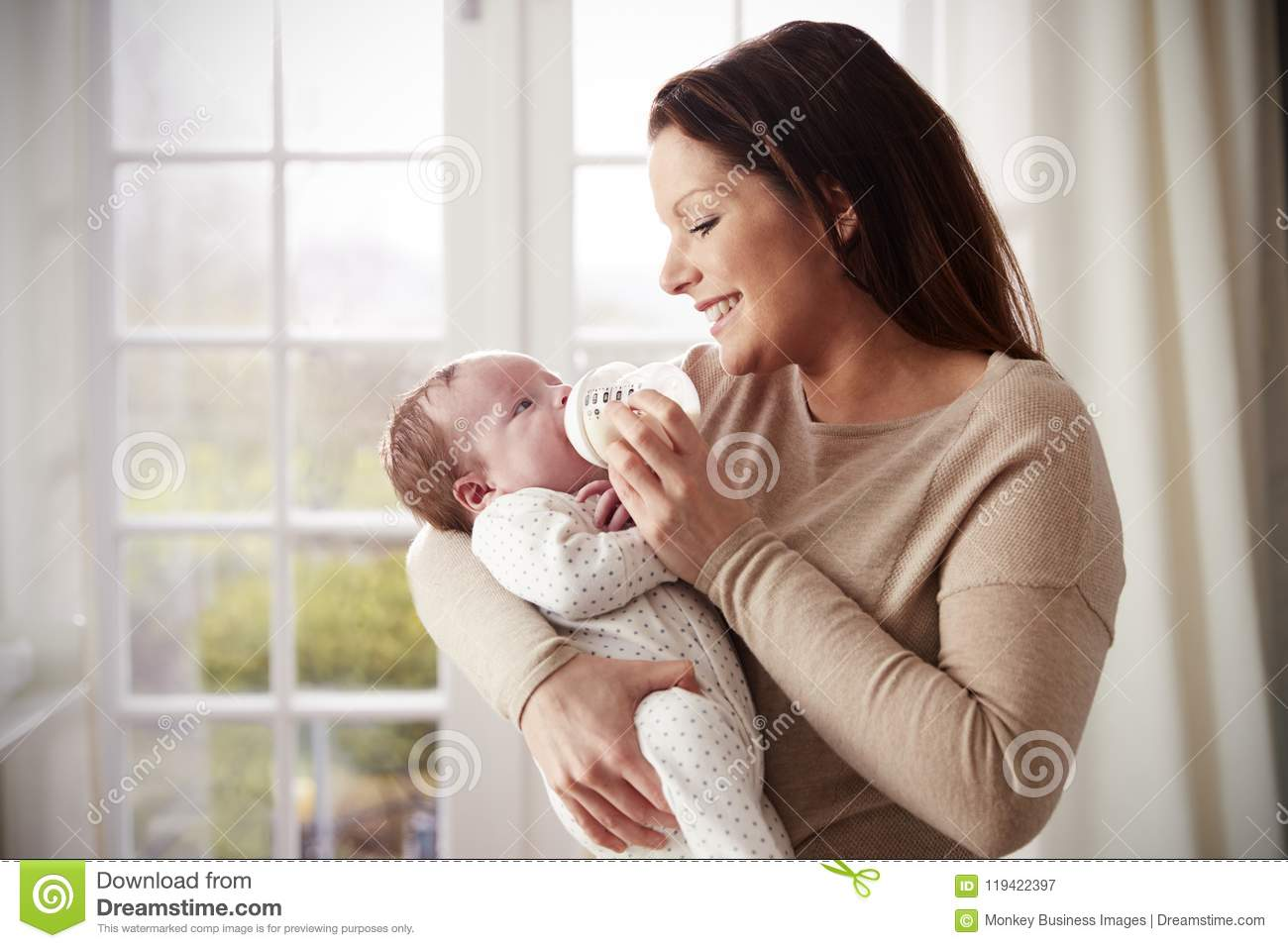 Mother Feeding Newborn Baby From Bottle At Home