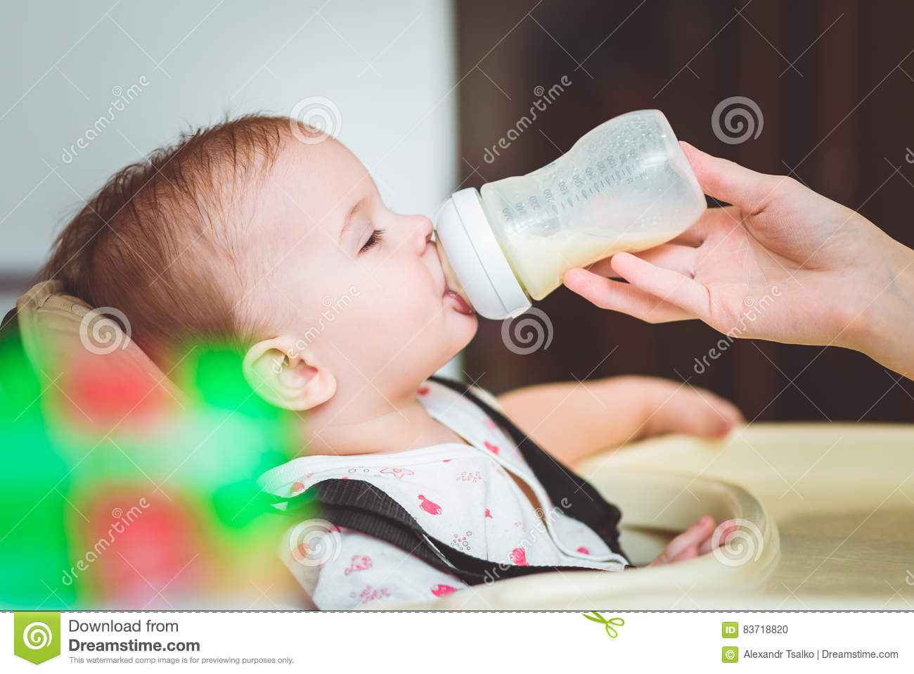 Mother Feeds Baby From A Bottle Of Milk Stock Photo