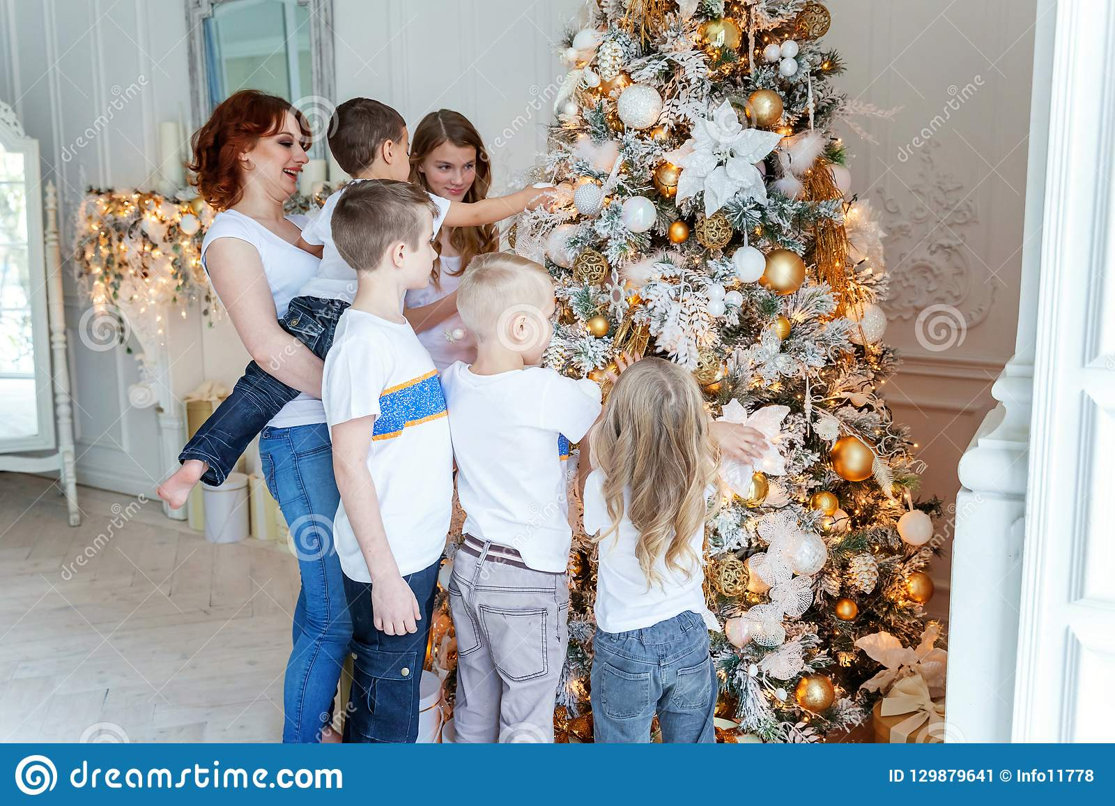 Mother and five children decorating Christmas tree at home
