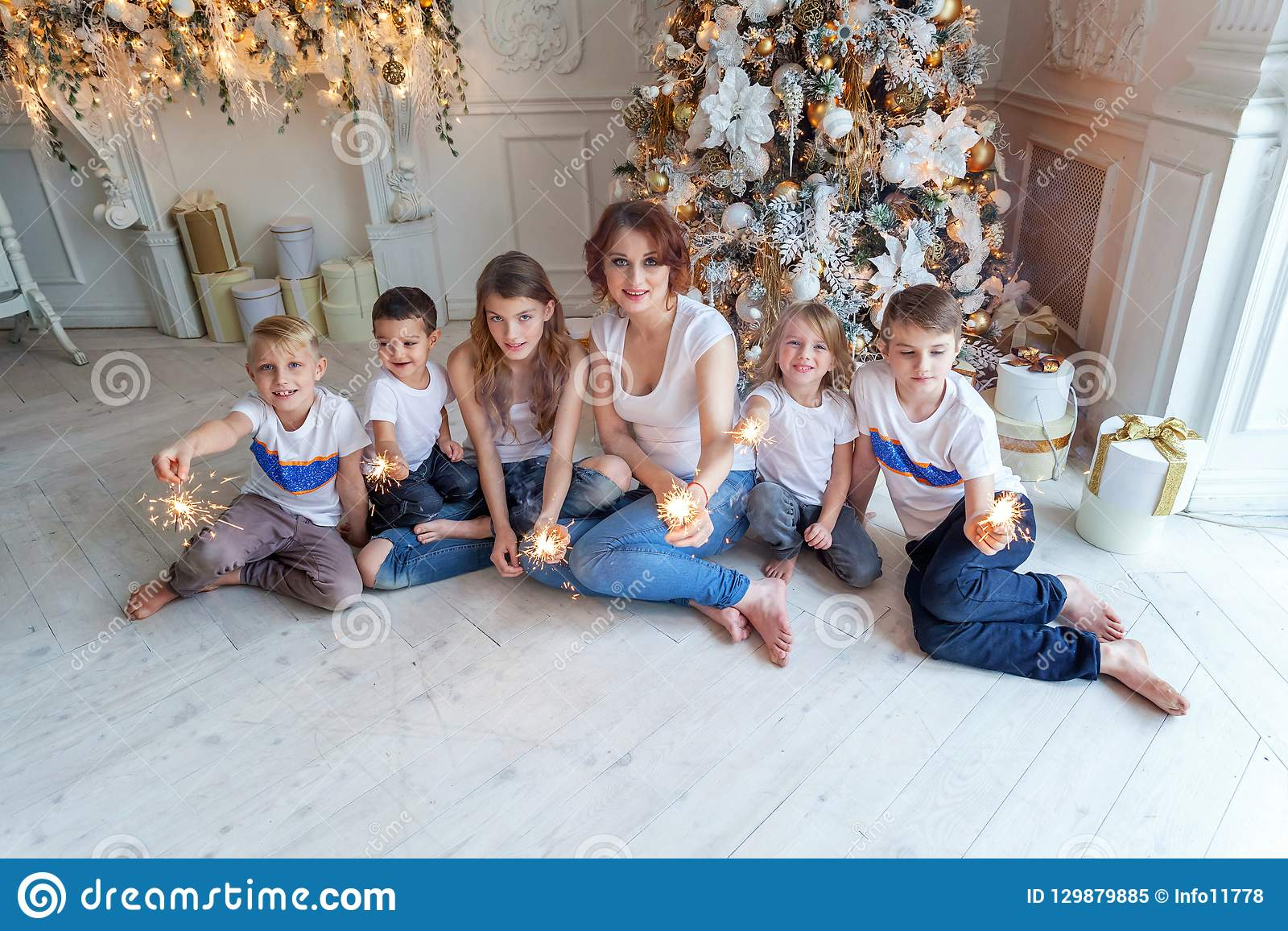 Mother and five children playing sparkler near Christmas tree at home