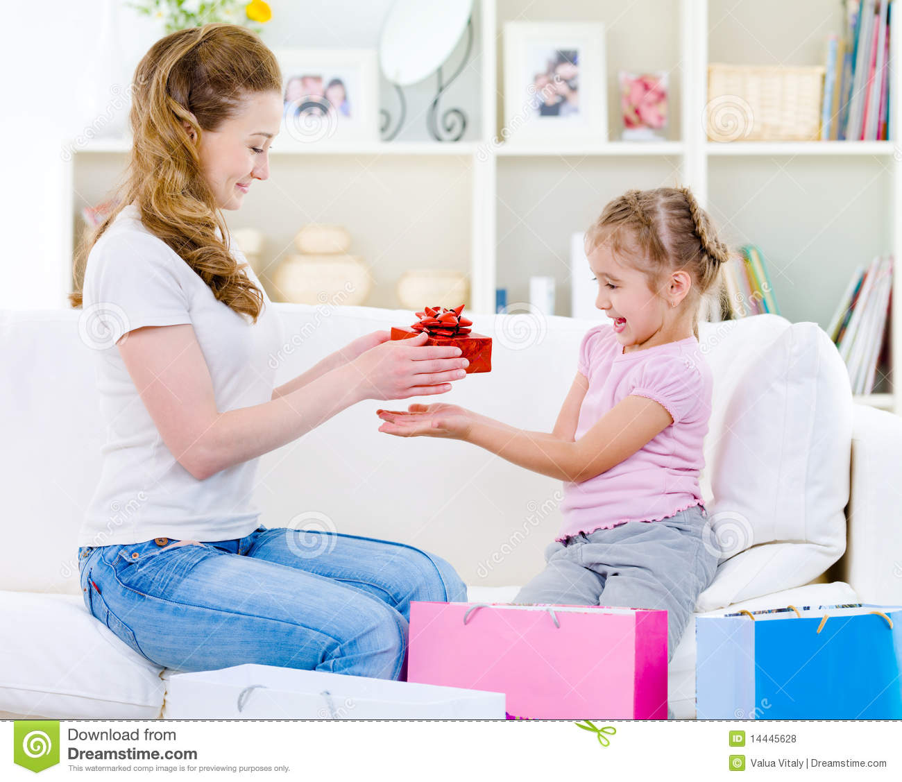 Beautiful mother giving a gift for her little pretty daughter - at ...