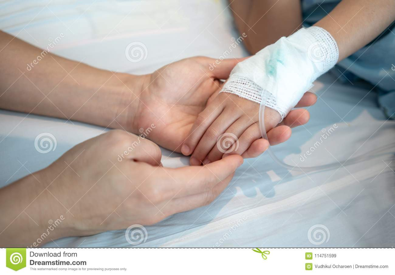Mother hands holding her baby patient hand with Saline intravenous
