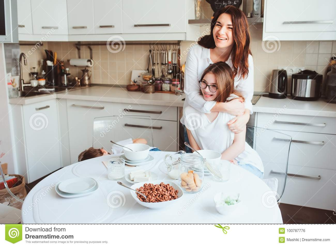 Mother Having Breakfast With Teen Daughter At Home In Modern White ...