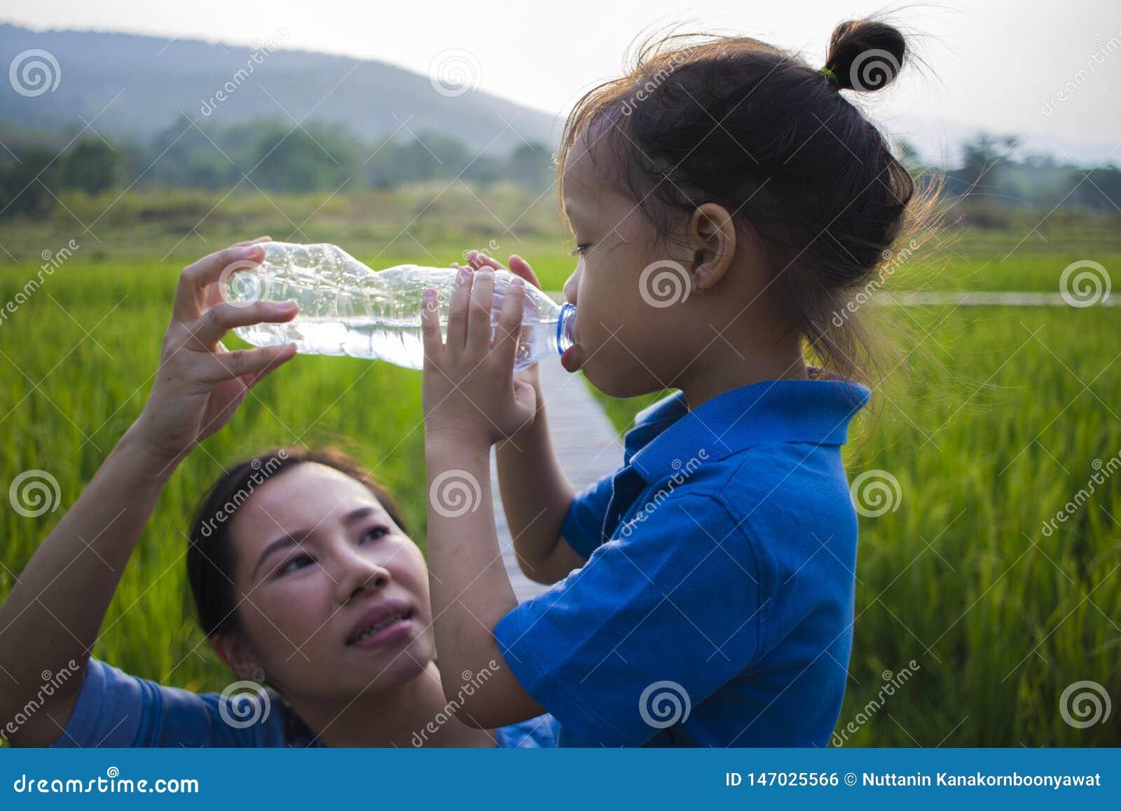 Mother help her children drinking water from bottle in rice field. long hair boy