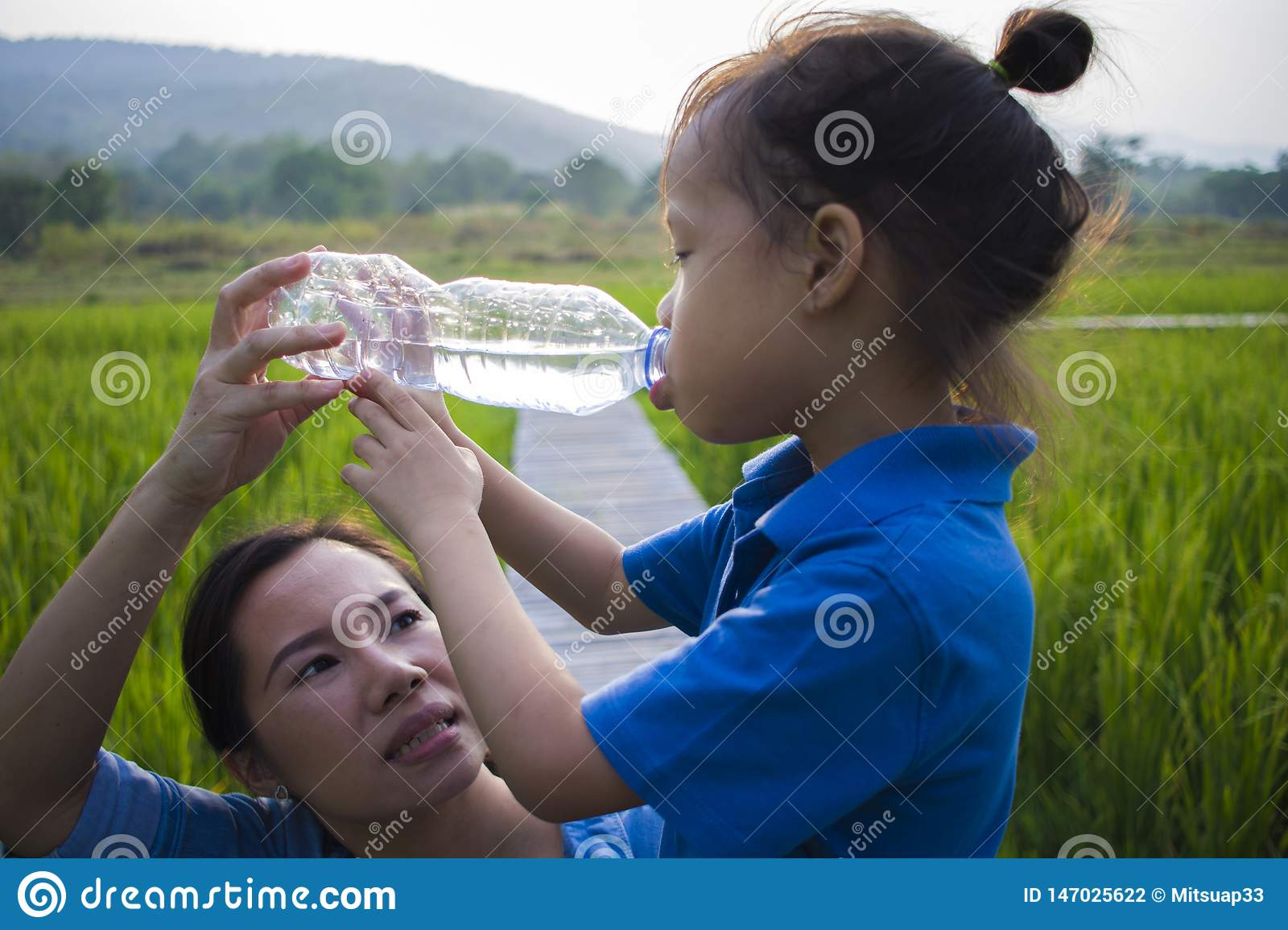 Mother help her children drinking water from bottle in rice field. long hair boy