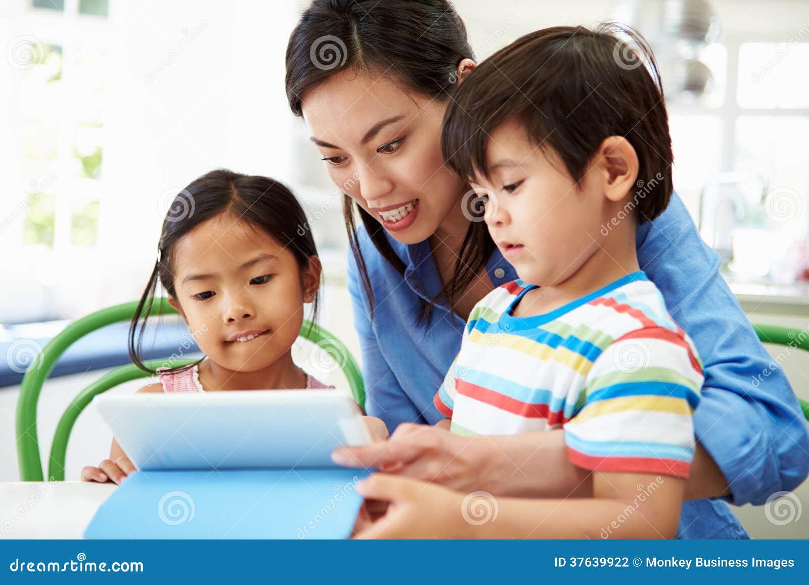 Mother Helping Children With Homework Using Digital Tablet