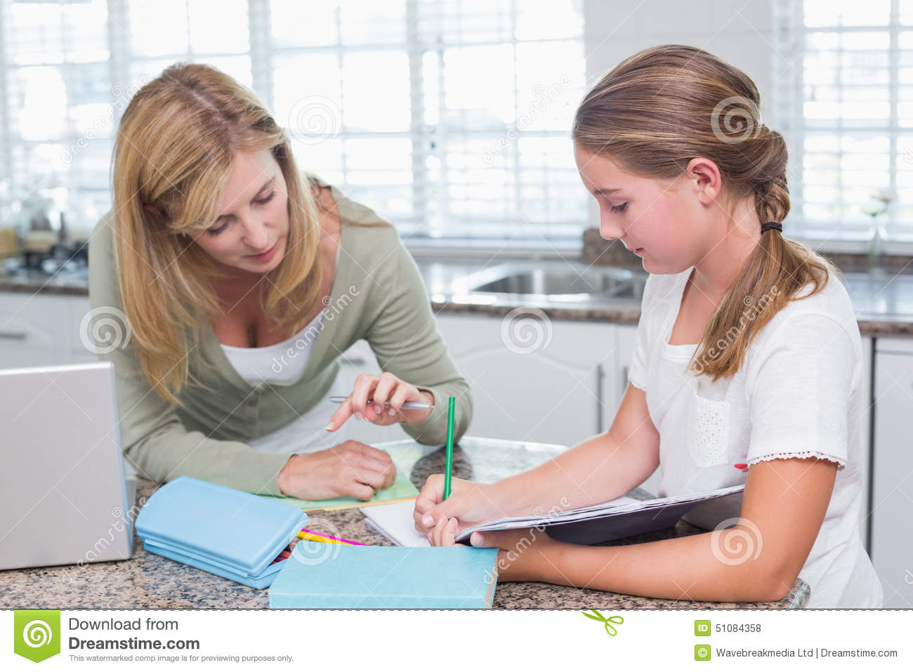 Mother Helping Daughter With Homework In Kitchen Stock Photo 35612448