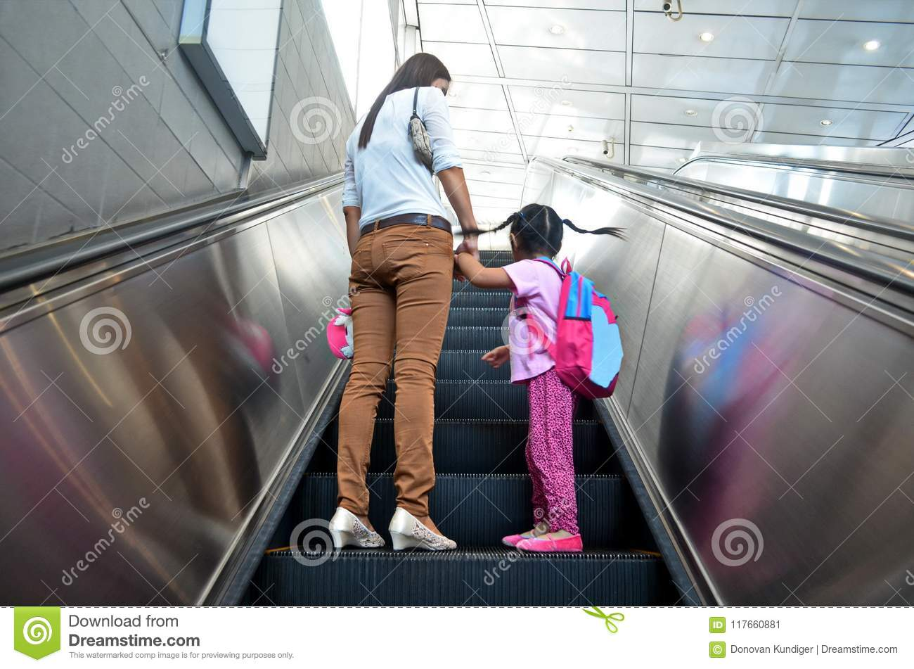 Mother helps alleviate fears on her daughter`s first ride on an escalator.