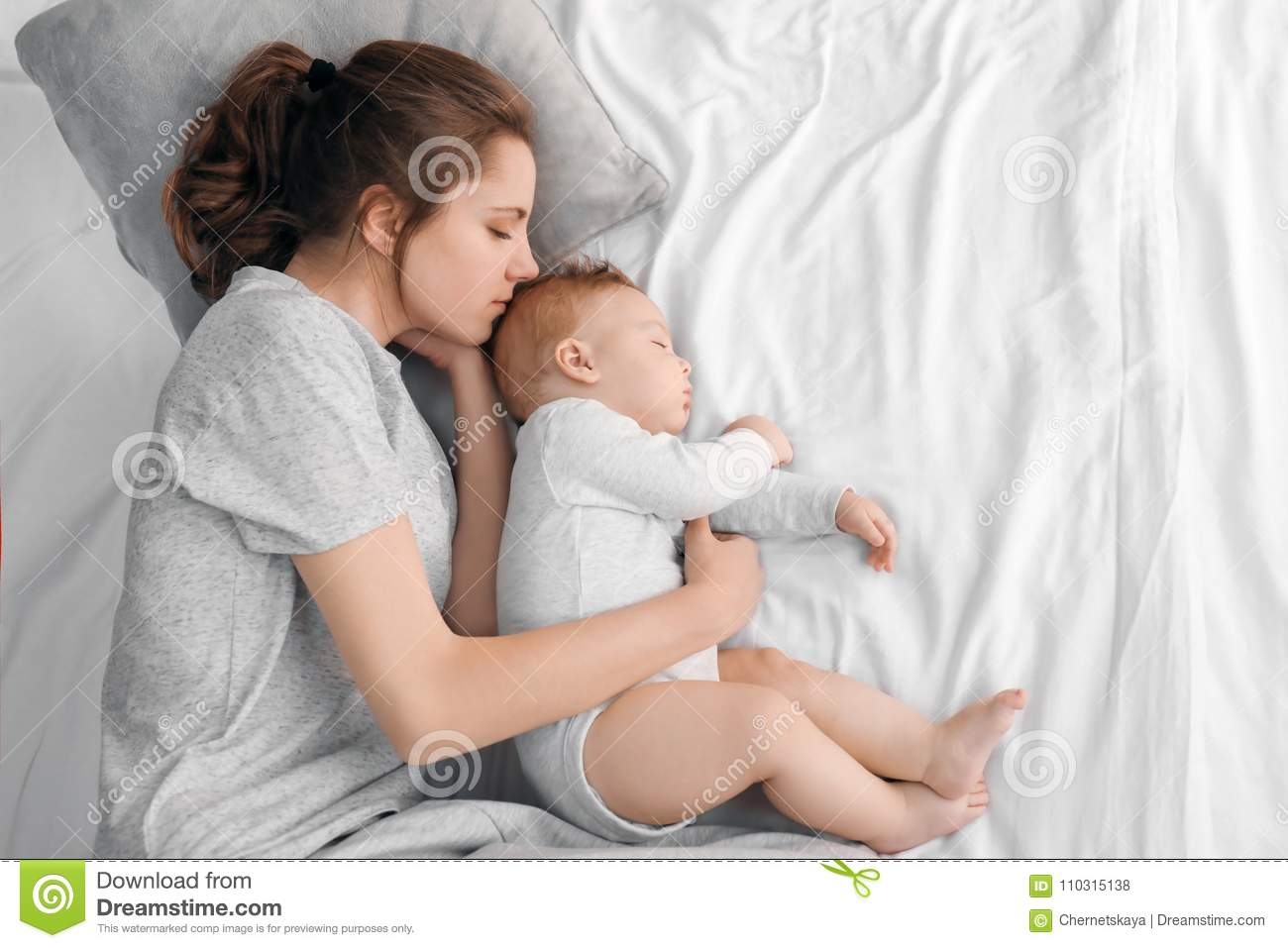 Mother with her baby sleeping on bed