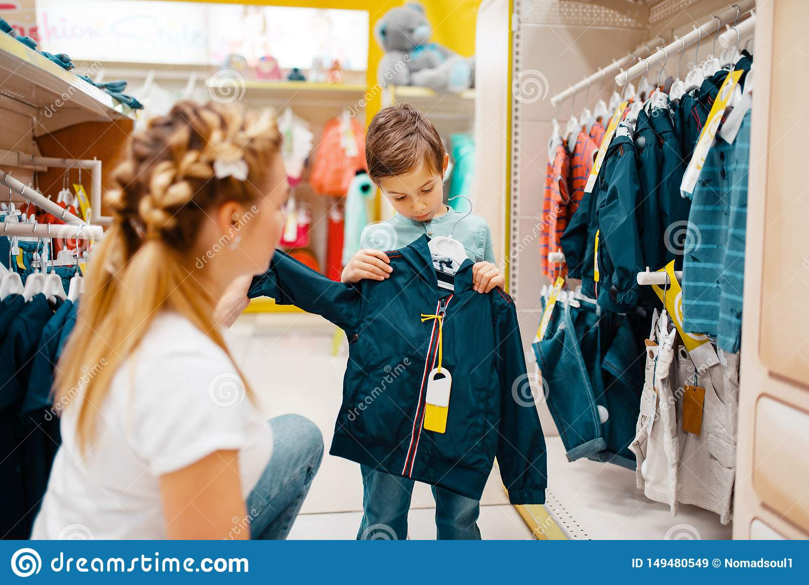 Mother With Her Boy Choosing Clothes In Kids Store Stock Image