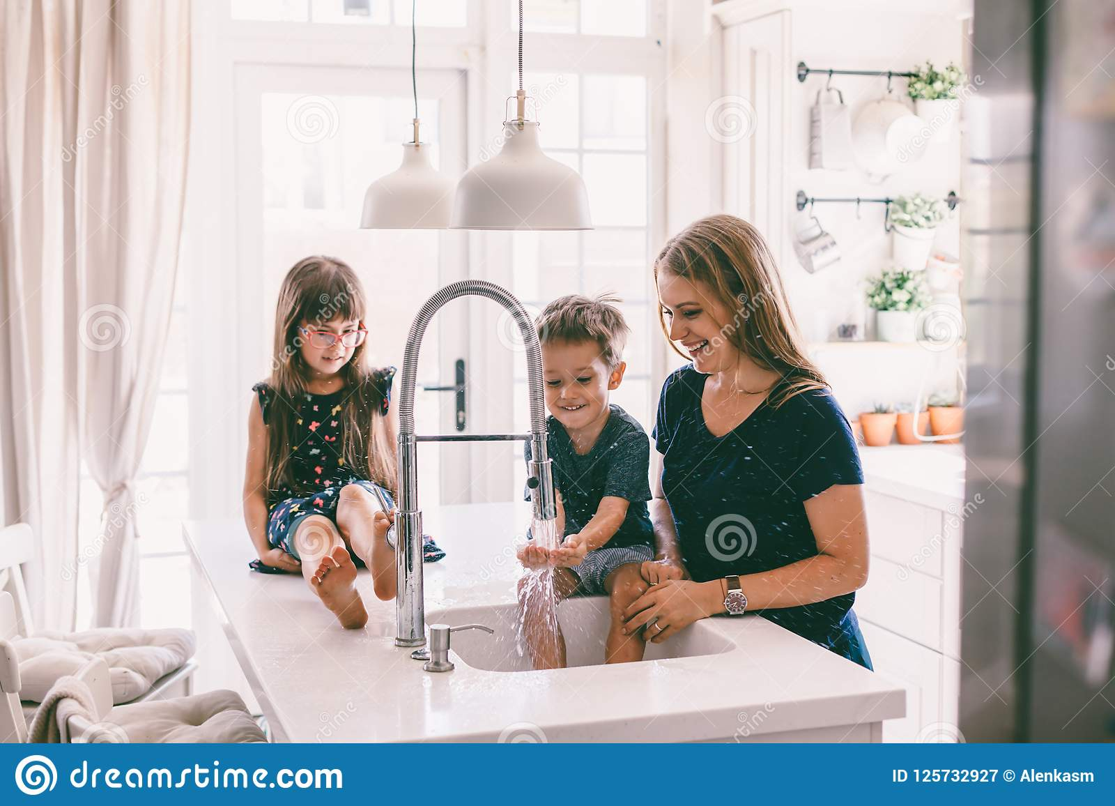 Mother with her children playing in kitchen sink