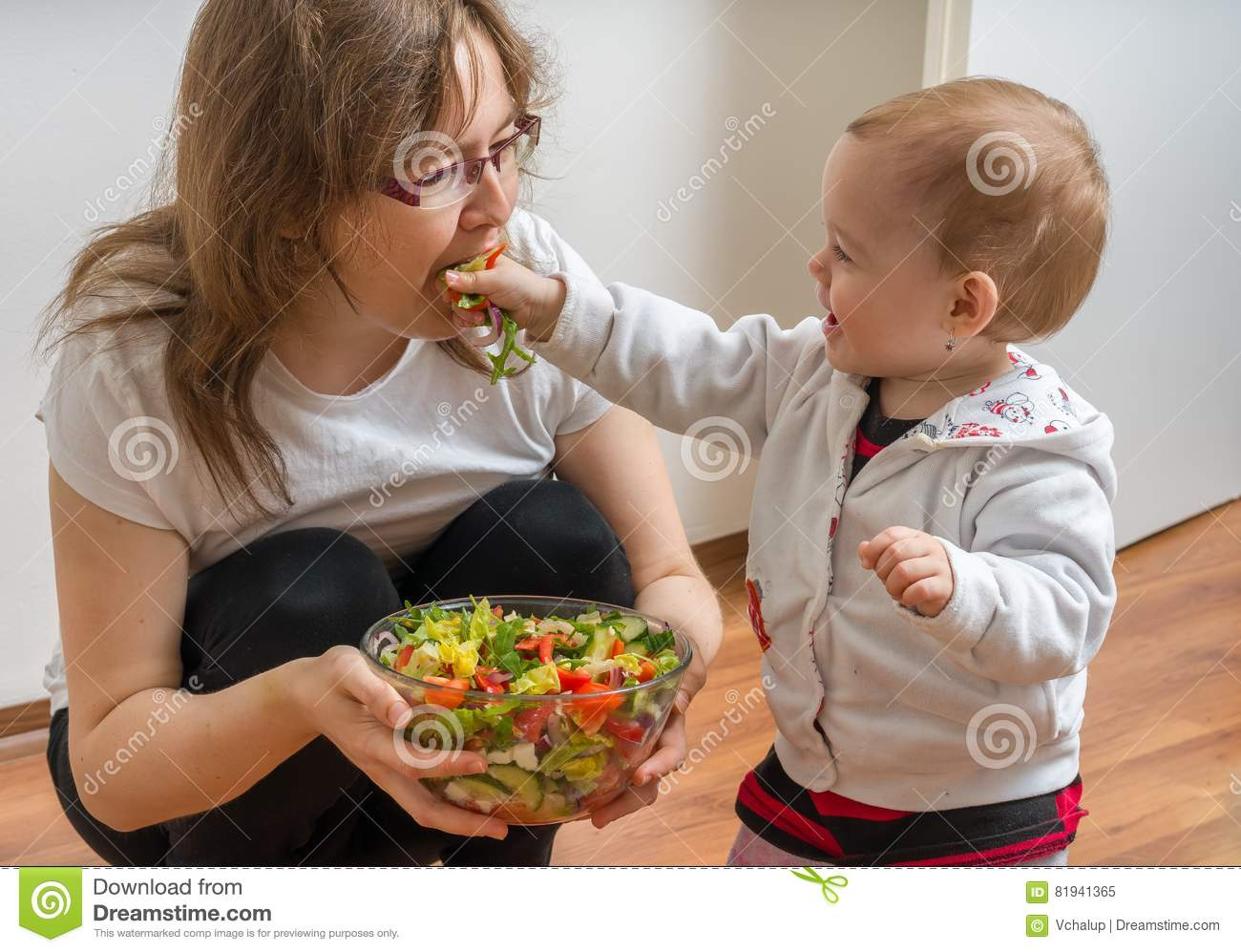 Mother and her daughter having fun and playing. Little child is feeding her mother with salad