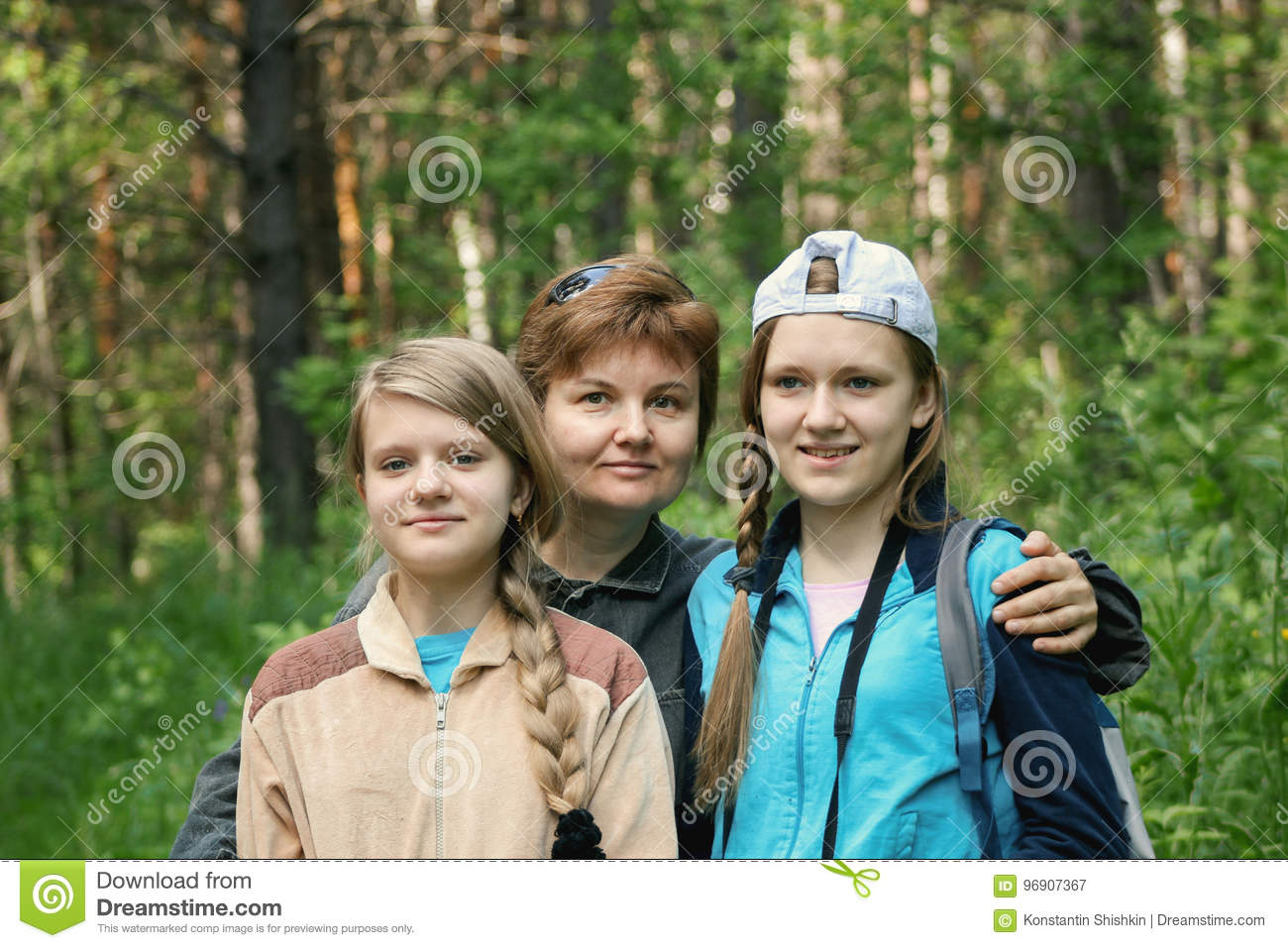 Mother and her daughters teenagers in park