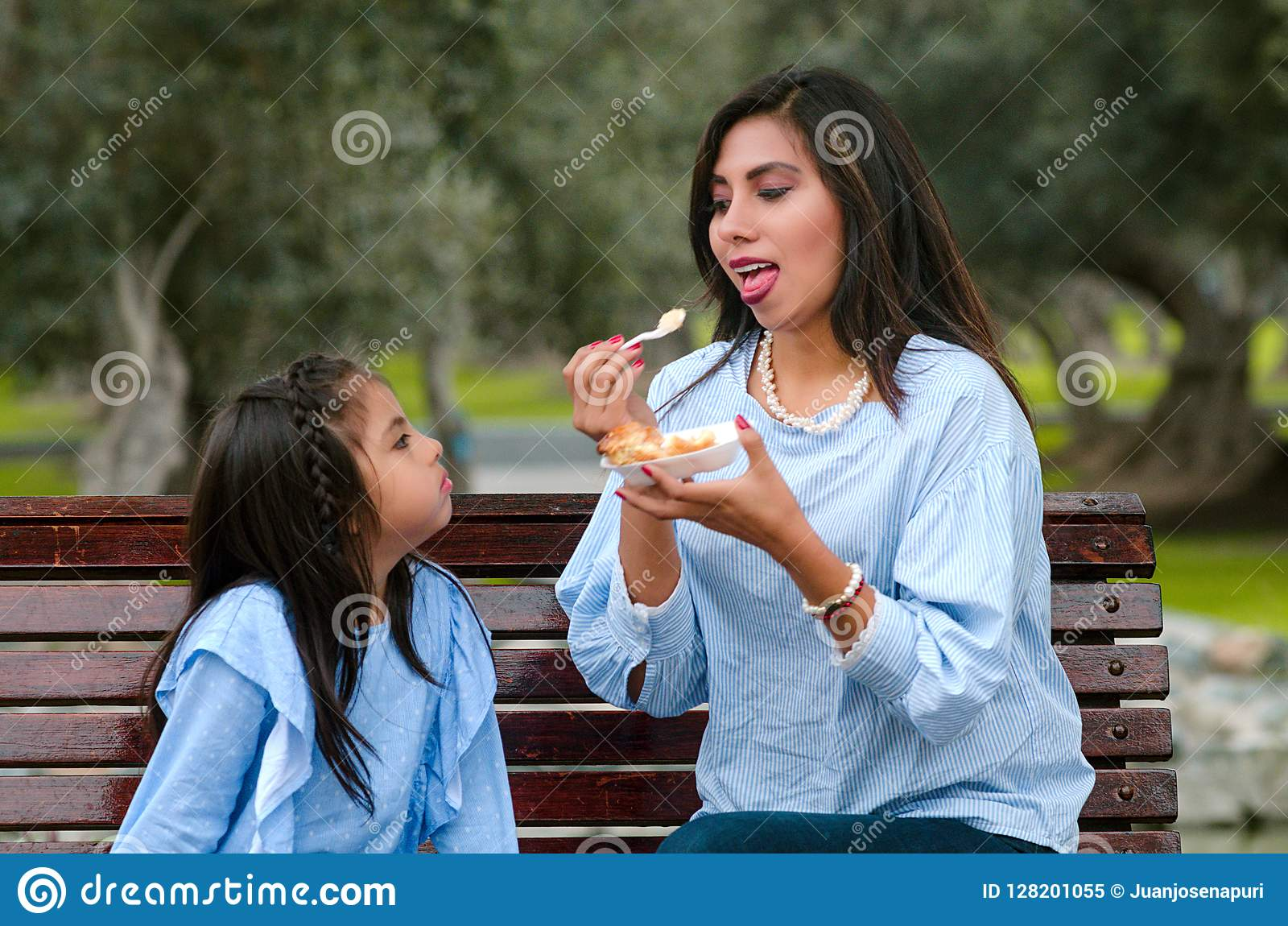 Mother and her little daughter sitting on a bench in the park