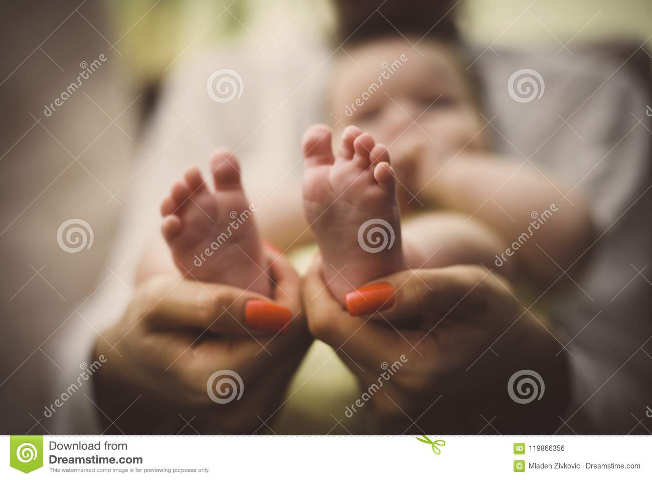 Mother holding baby feet in hands. Focus on feet.