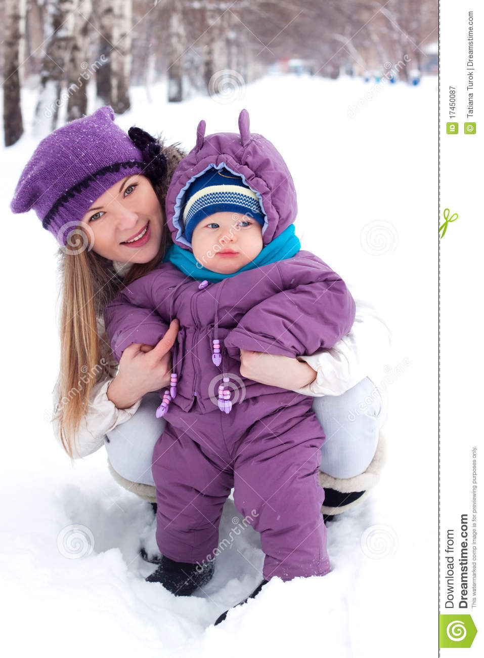 Mother holding a baby, snow, winter park, walk