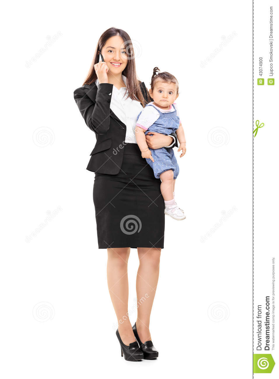 Mother holding her daughter and talking on phone