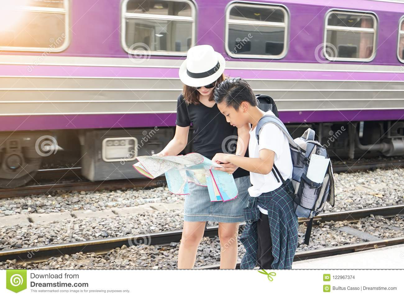 Mother holding a map and son looking for travel by the train.