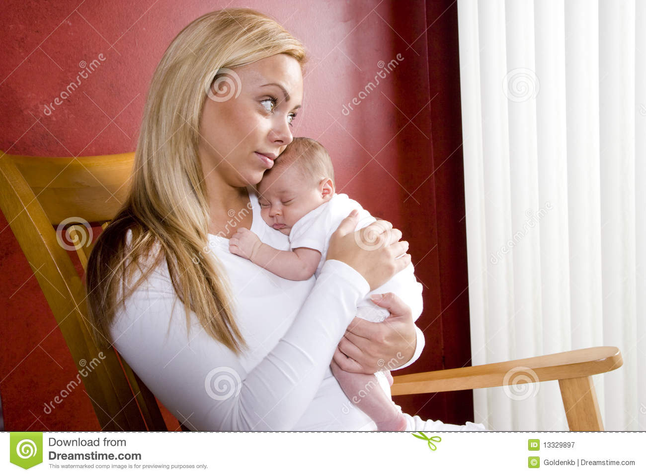 Mother Holding Newborn Baby In Rocking Chair Stock Image