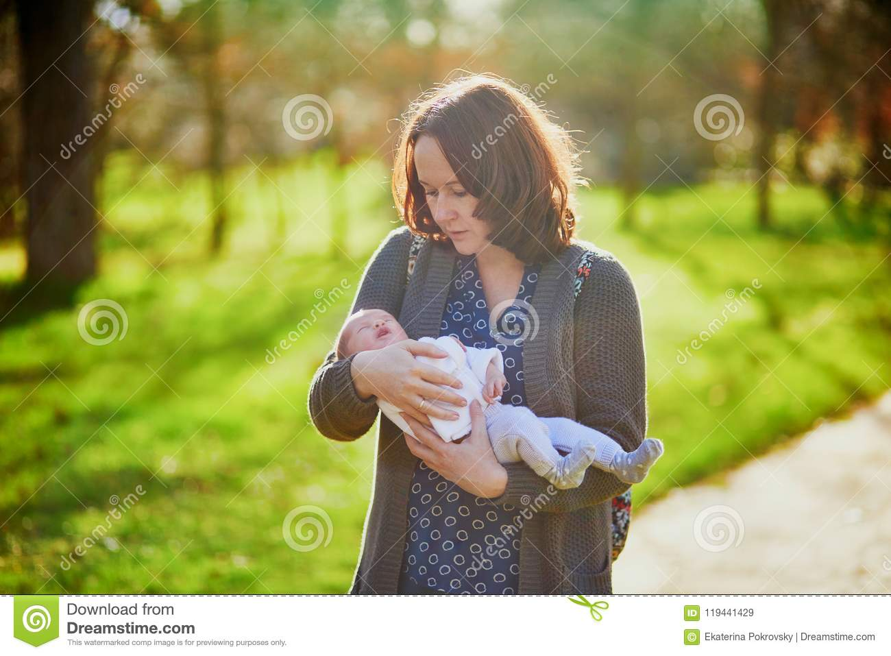 e6950a511 Mother holding 4 weeks old baby girl in her arms. 1 month old child in  mommy`s hands outdoors. First walk for a newborn