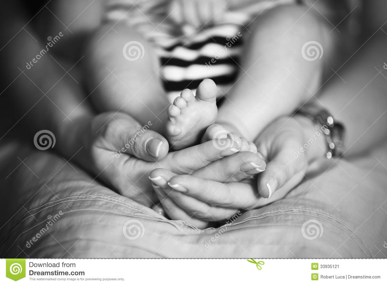 Mother holds baby feet in hands