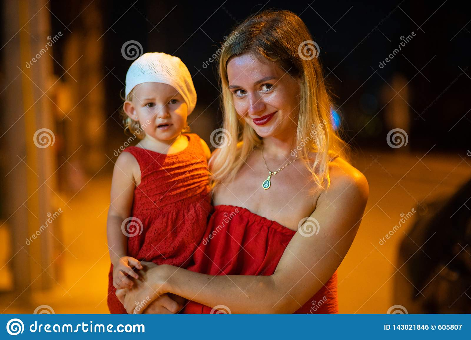 Mother holds daughter in her arms, mother with daughter is dressed in red dresses, child in white beret, at night.