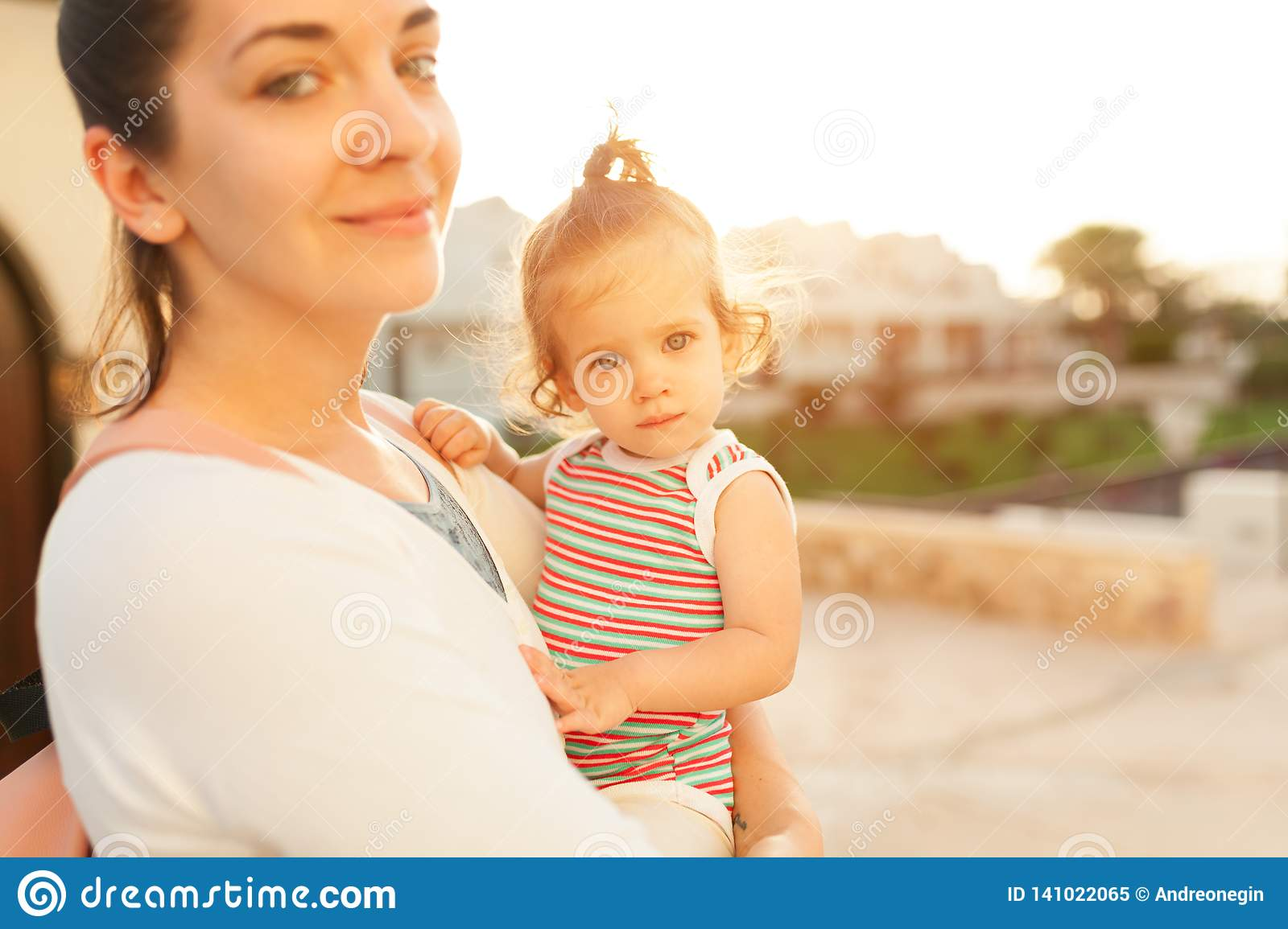 Mother hugging with her little daughter outdoor in nature on sunny day Positive human emotions, feelings, emotions.