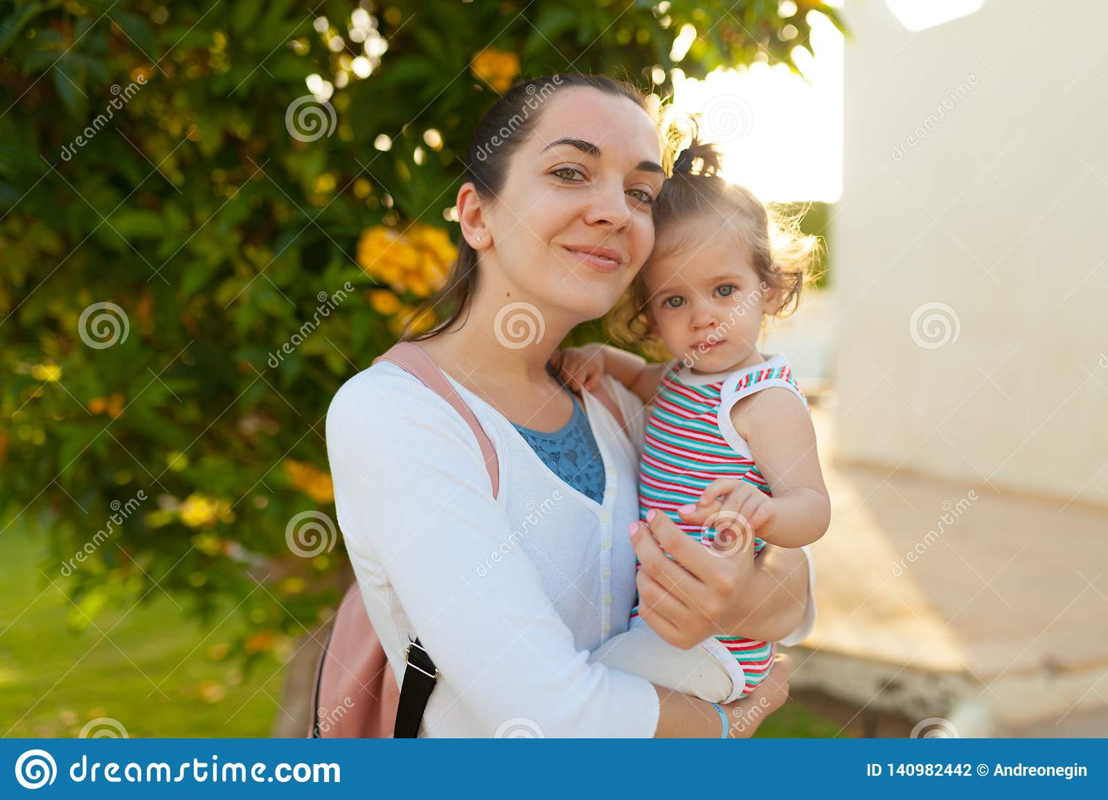 Mother hugging with her little daughter outdoor in nature on sunny day Positive human emotions, feelings, emotions
