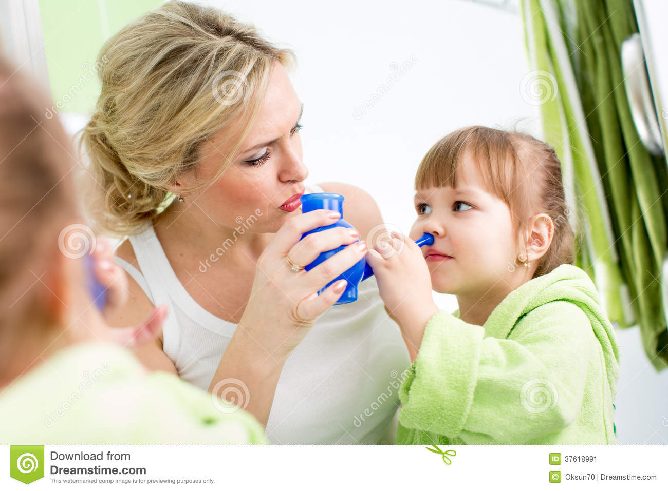 Mother and kid with neti pot for nasal irrigation