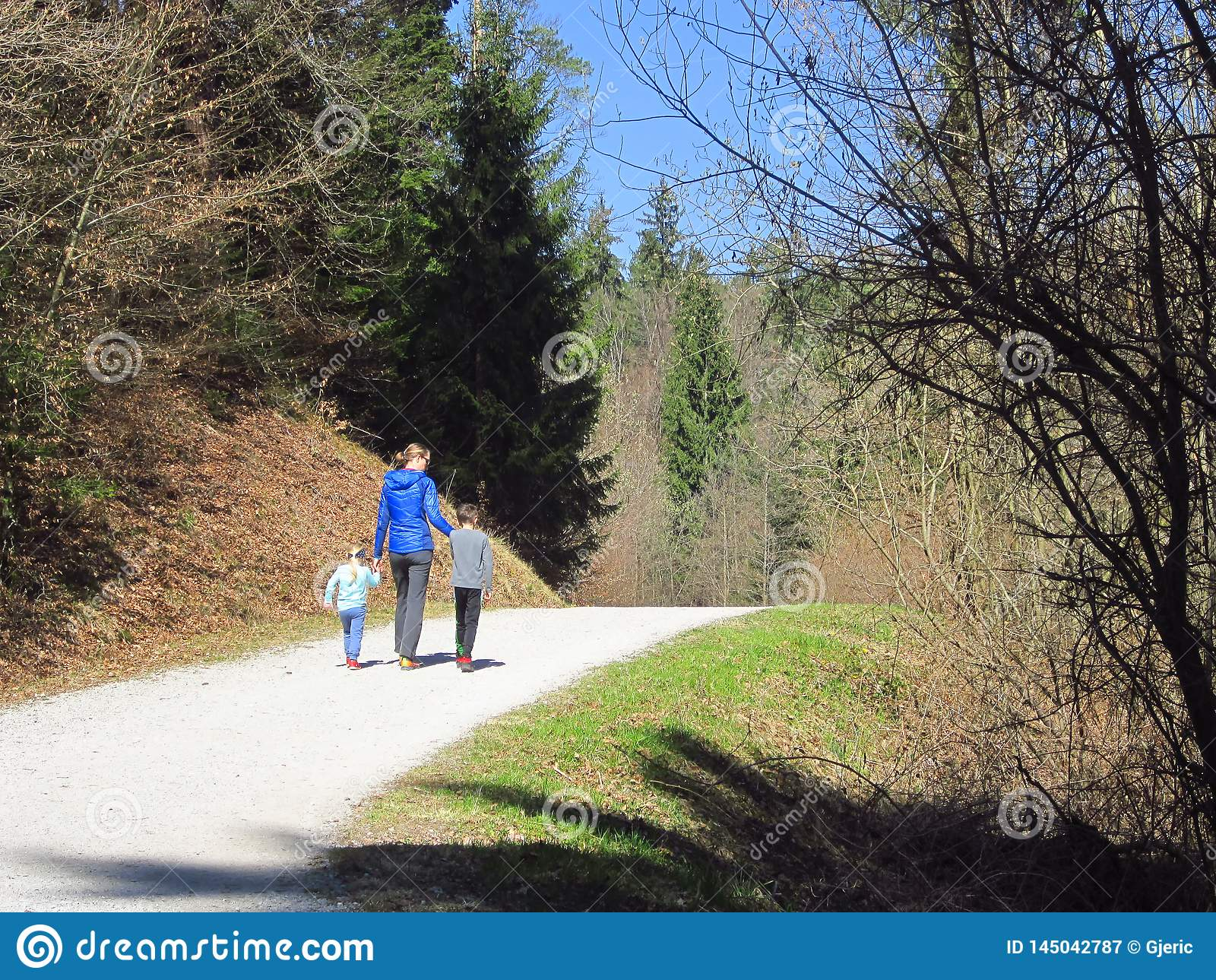 Mother with kids hiking in forest