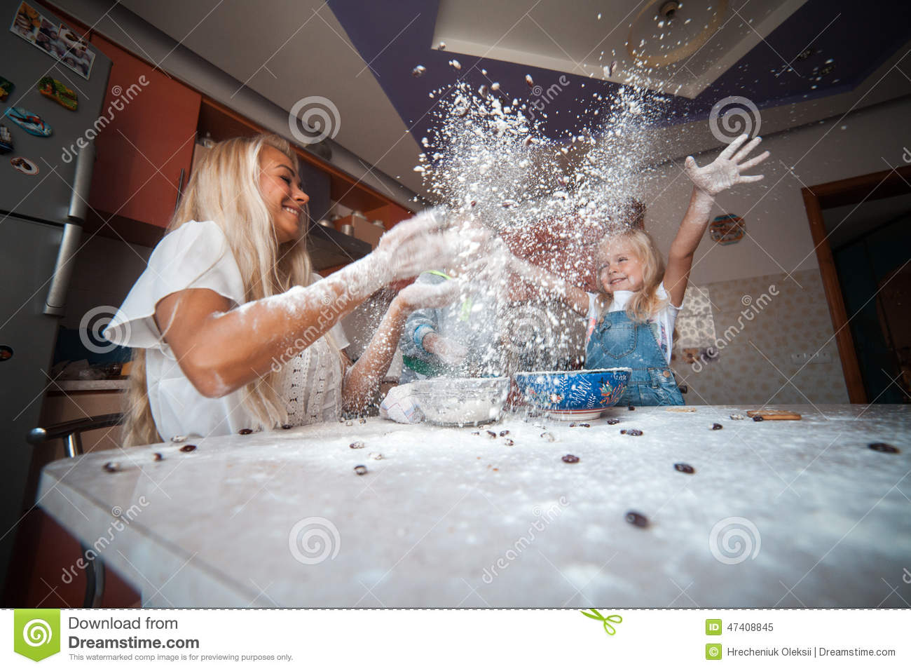 Mother With Kids On Kitchen Throw Flour To The Top Stock
