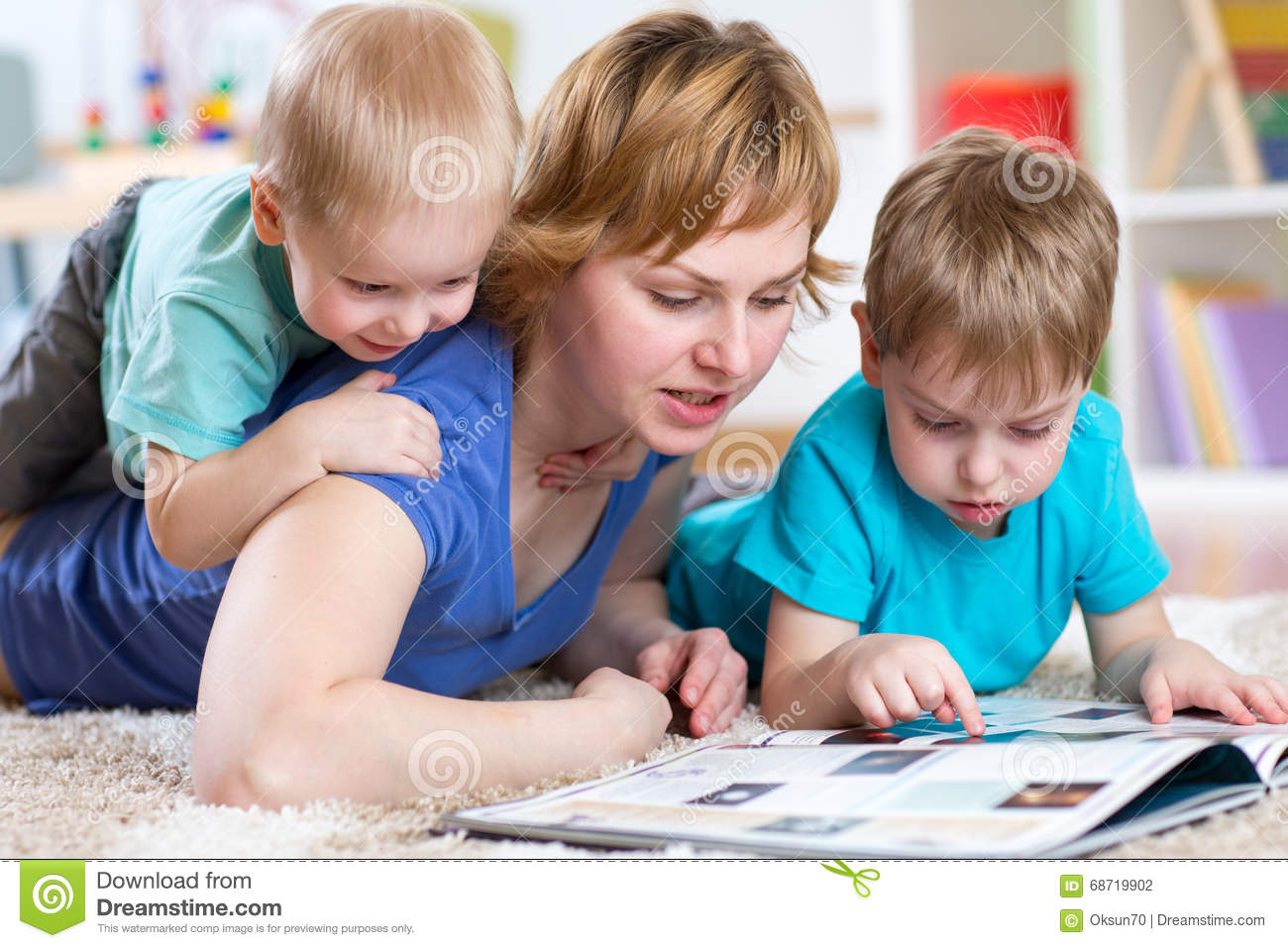 Mother And Kids Reading Book At Home Stock Photo