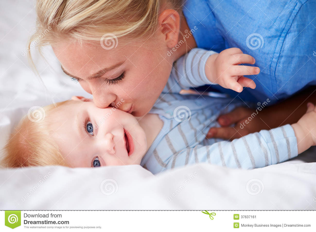 mother kissing baby son as they lie in bed together stock image image 37637161. Black Bedroom Furniture Sets. Home Design Ideas
