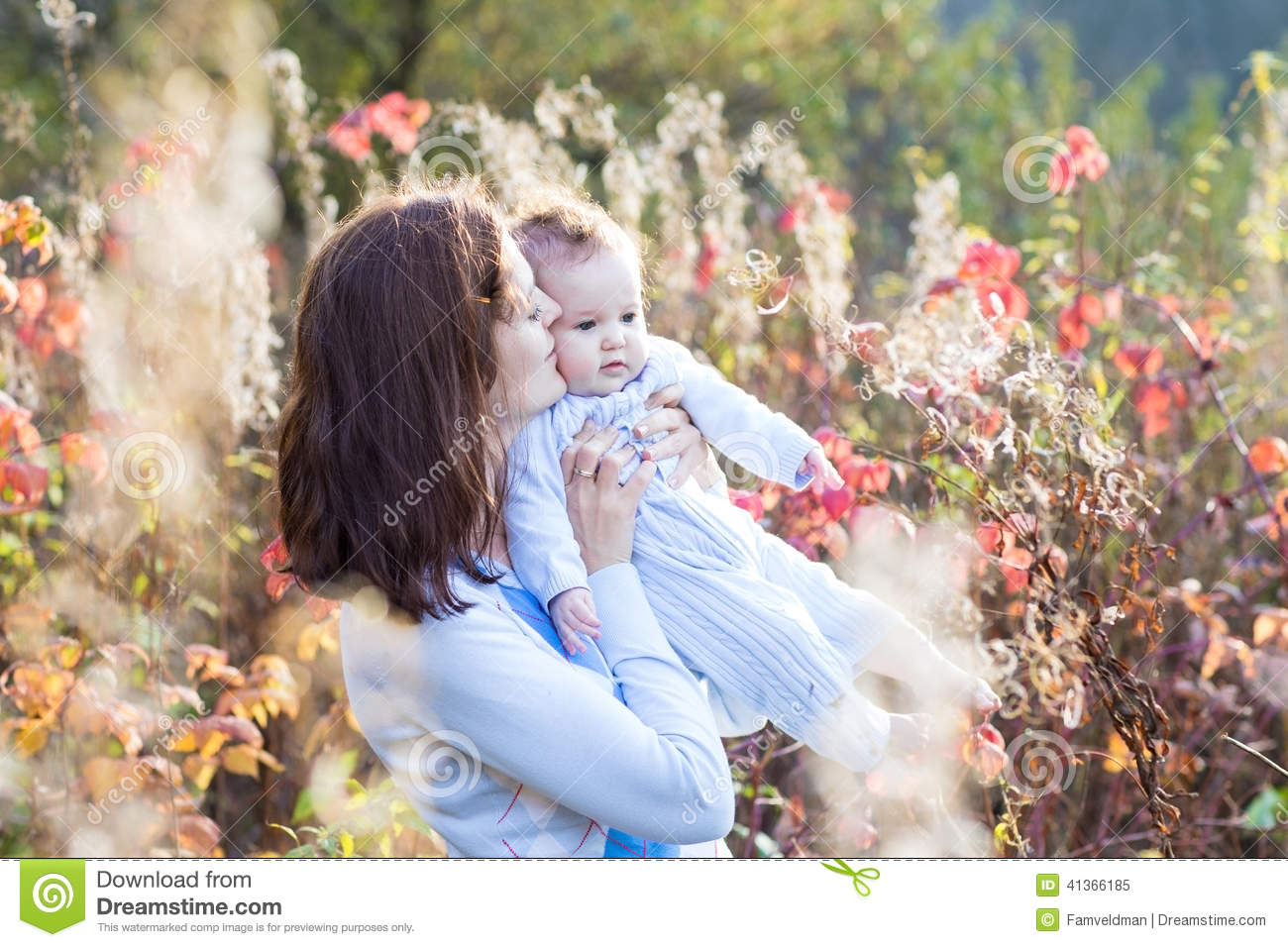 Mother kissing her baby daughter on walk in autumn park