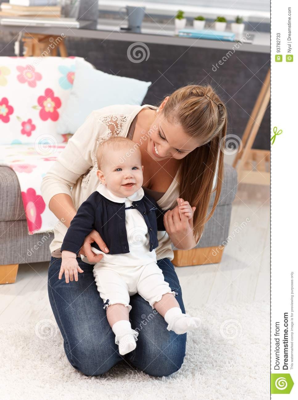Mother kneeling on floor with baby girl on lap