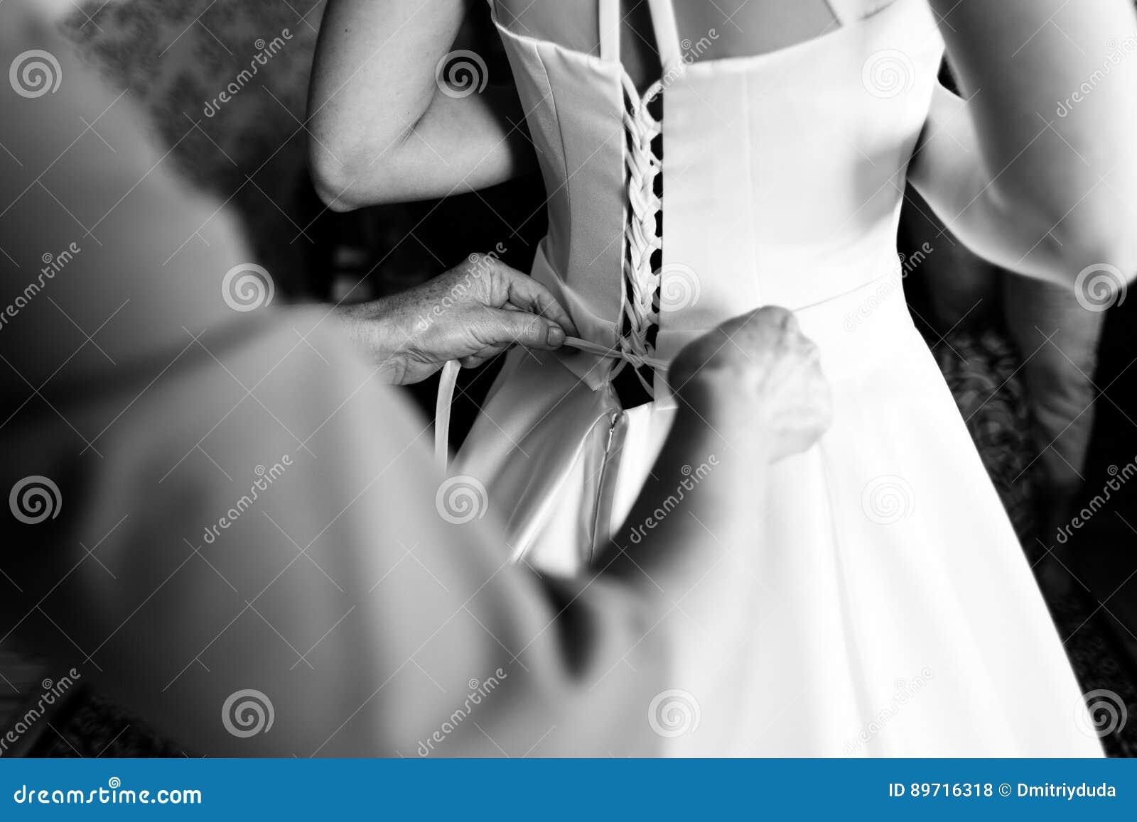 Mother laces the bride`s dress