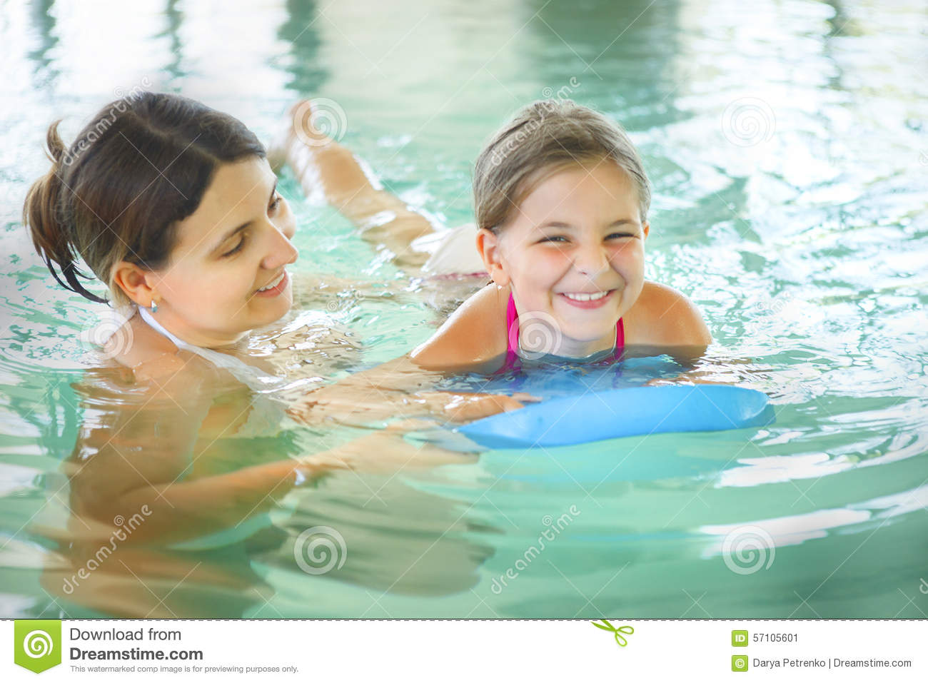 mother learning to swim her little daughter in an indoor swimmin stock photo image 57105601