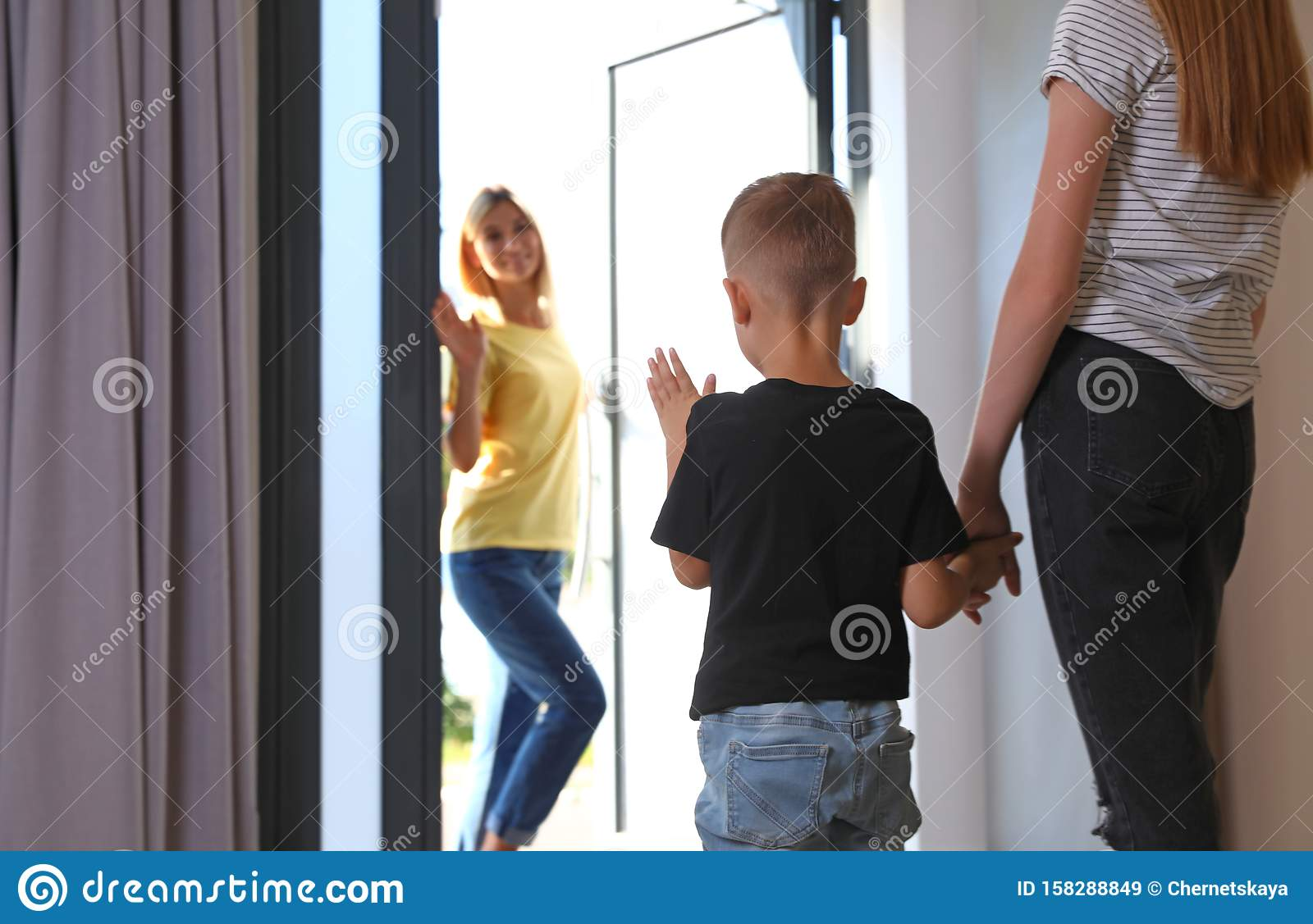 Mother leaving her little son with nanny at home. Space for text