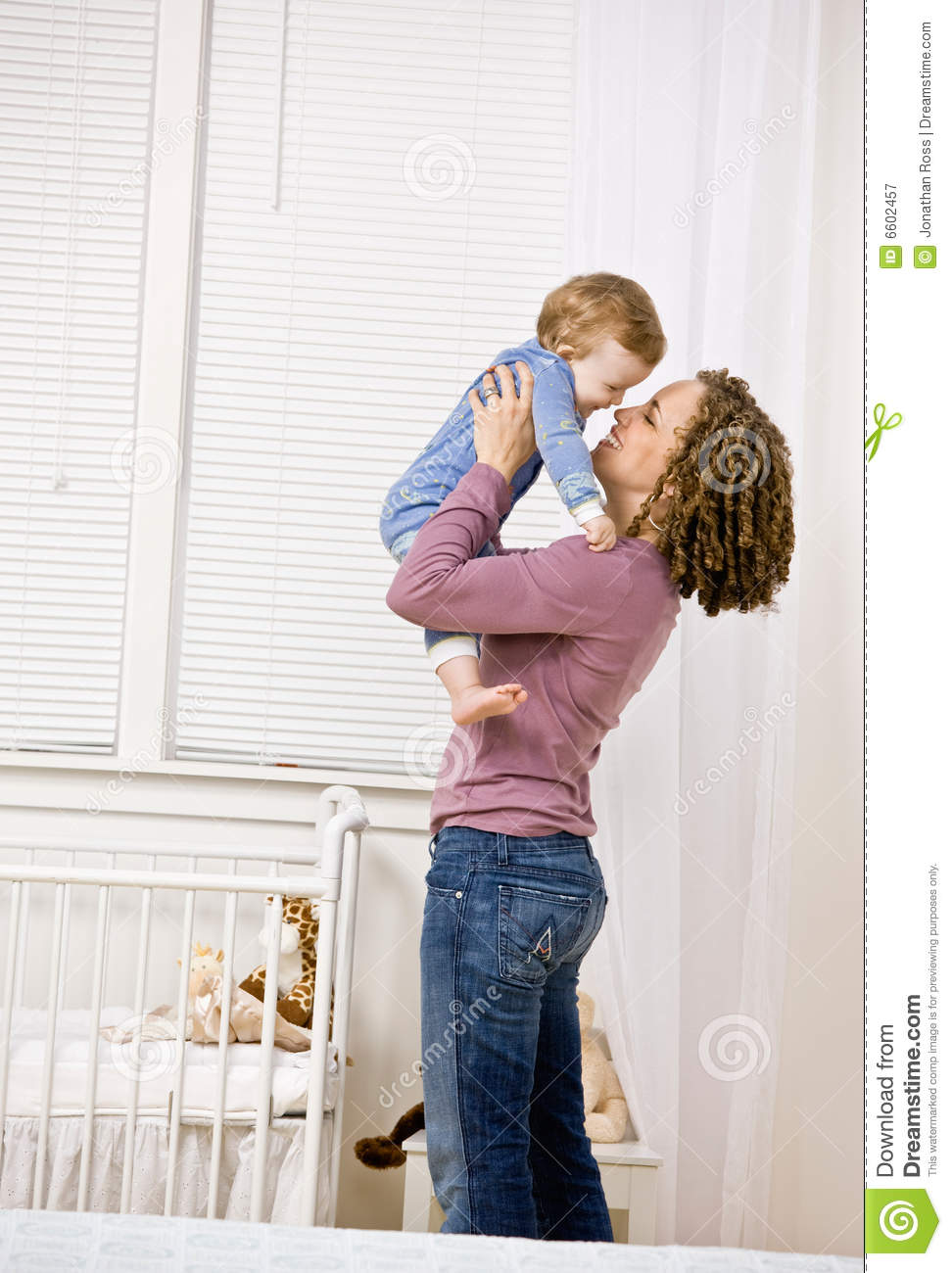 mother lifting son from crib in bedroom royalty free stock