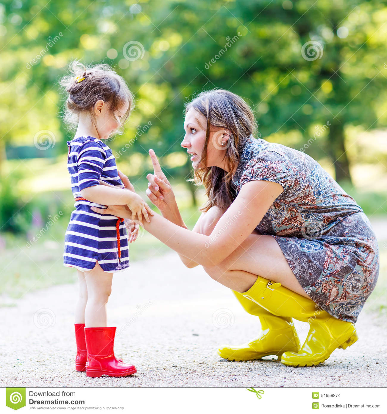 Young Happy Beautiful Family Playing Together On The Beach: Mother And Little Adorable Child In Yellow Rubber Boots