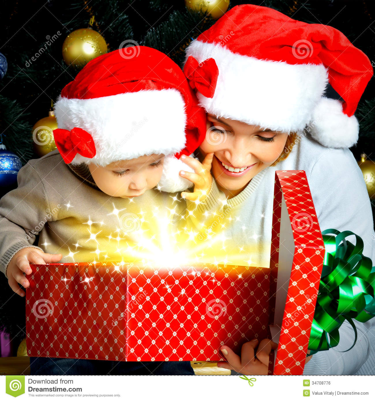 Mother With Little Child Opens The Box With Gifts On