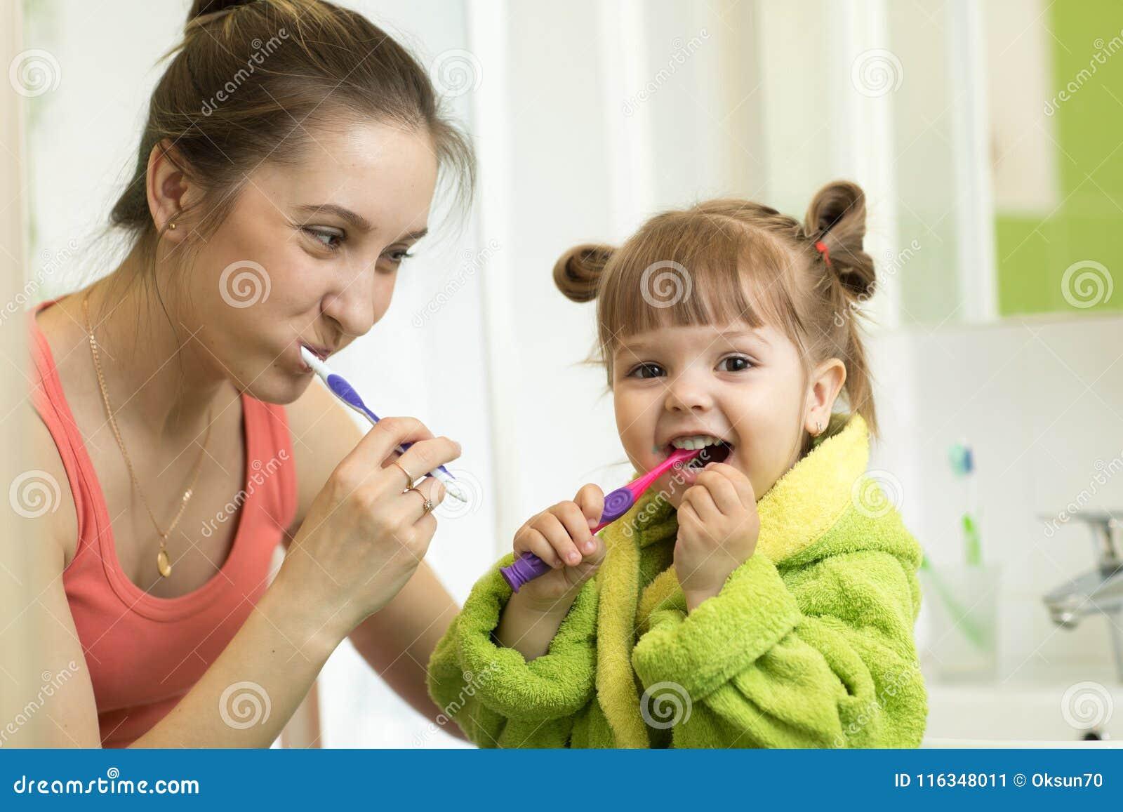 Beautiful Mother And Kid Brushing Teeth In Bathroom Stock